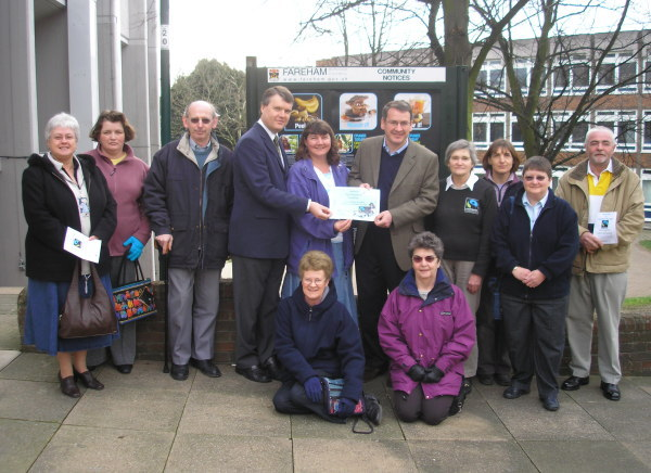 Seán Woodward, Working Group chair Rachel Hicks and Mark Hoban show the certificate of Fareham's Fairtrade status, flanked by members of the group.