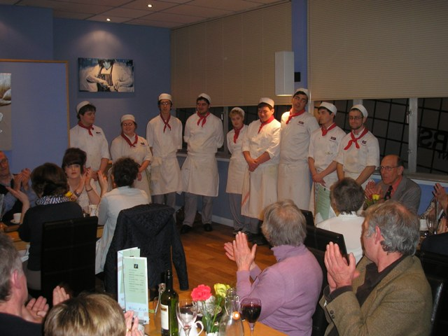 The chefs who prepared the meal receive the applause of the diners.
