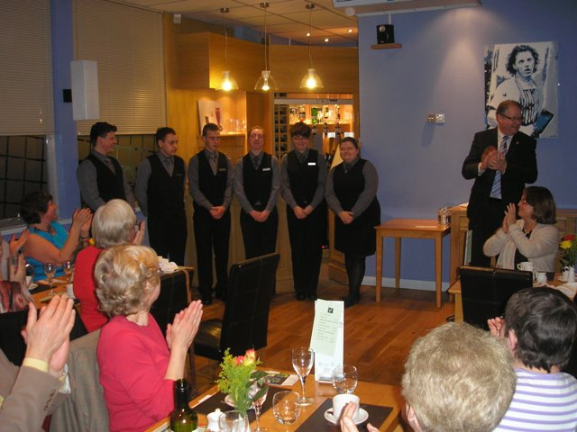 The students who served the meal receive the applause of the diners.